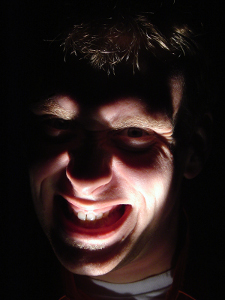 A man with a flashlight below his face grinning evilly.