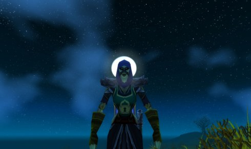 Maiheela stands with the moon directly behind her head.